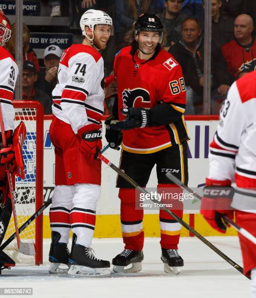 Jaromir Jagr of the Calgary Flames shares a laugh with Jaccob Slavin of the Carolina Hurricanes after the whistle at Scotiabank Saddledome on October...