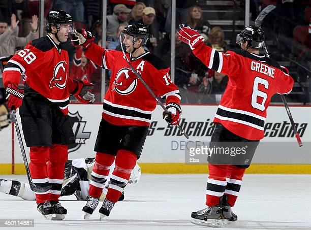 Jaromir Jagr of the New Jersey Devils is congratulated by teammates Travis Zajac and Andy Greene after Jagr scored an empty net goal in the third...