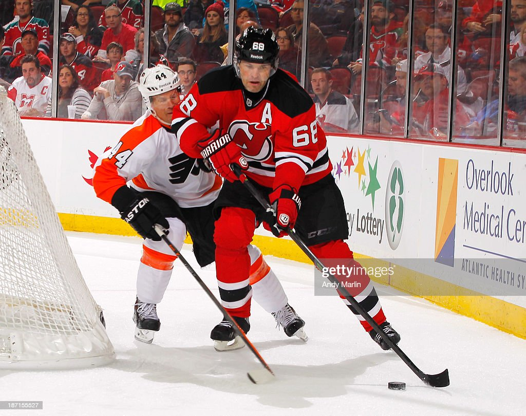 Jaromir Jagr #68 of the New Jersey Devils plays the puck against Kimmo Timonen #44 of the Philadelphia Flyers during the game at the Prudential Center on November 2, 2013 in Newark, New Jersey.