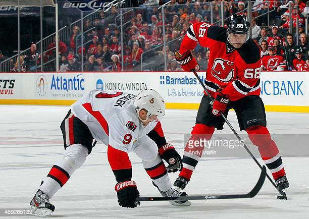 Jaromir Jagr of the New Jersey Devils plays the puck while being defended by Milan Michalek of the Ottawa Senators during the game at the Prudential...