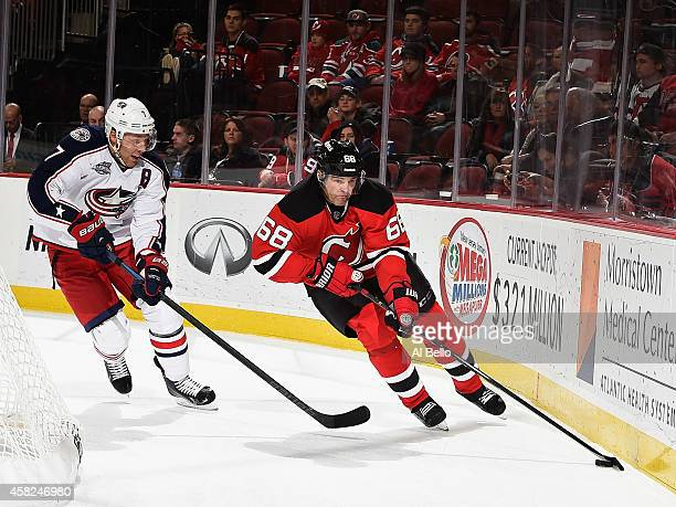 Jaromir Jagr of the New Jersey Devils skates with the puck as Jack Johnson of the Columbus Blue Jackets defends during their game at the Prudential...