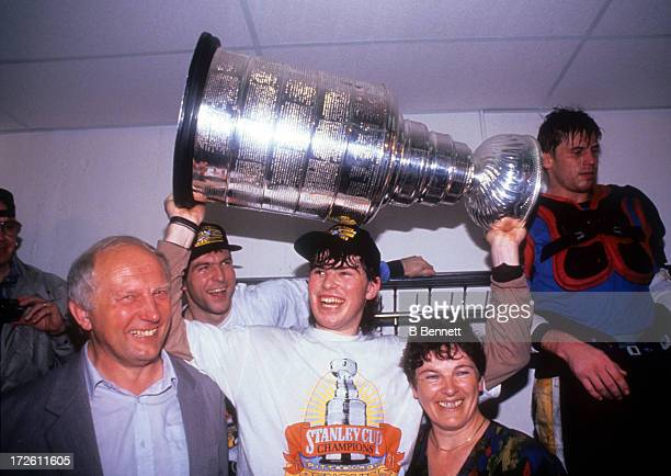 Jaromir Jagr of the Pittsburgh Penguins holds the Stanley Cup with his parents in the locker room after Game 6 of the 1991 Stanley Cup Finals against...