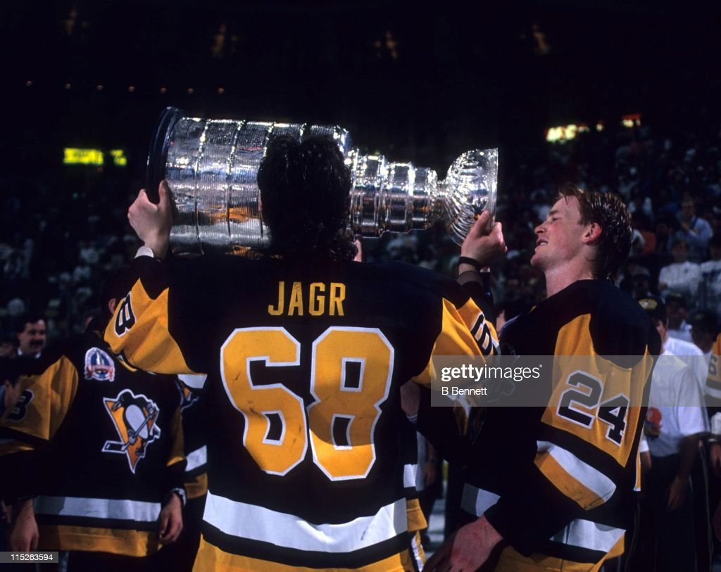 Jaromir Jagr of the Pittsburgh Penguins kisses the Stanley Cup as teammate Troy Loney waits his turn after Game 4 of the 1992 Stanley Cup Finals...