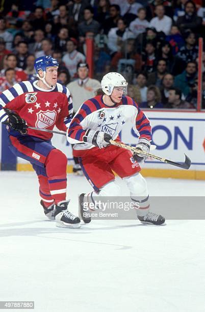 Jaromir Jagr of the Wales Conference and the Pittsburgh Penguins skates on the ice as he is defended by Mark Tinordi of the Campbell Conference and...