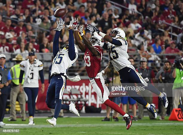 Jaron Brown of the Arizona Cardinals battles for the ball with Richard Crawford and Darrell Stuckey ofthe San Diego Chargers during the second...