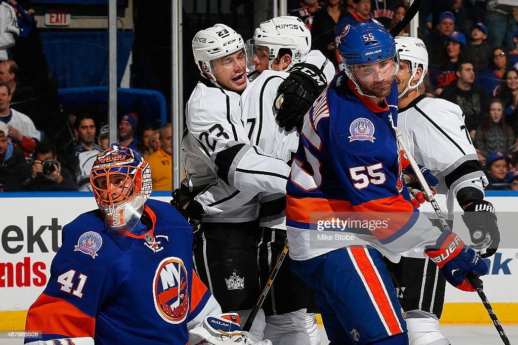 Jaroslav Halak and Johnny Boychuk of the New York Islanders look on as Nick Shore of the Los Angeles Kings is congratulated by teammate Dustin Brown...