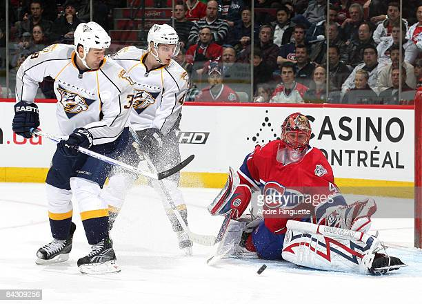 Jaroslav Halak of the Montreal Canadiens makes a pad save as Vernon Fiddler and Antti Pihlstrom of the Nashville Predators position themselves for a...