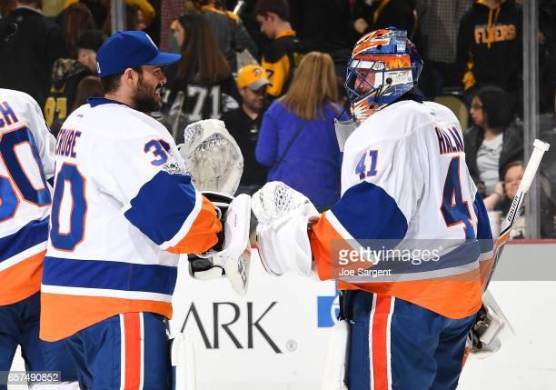 Jaroslav Halak of the New York Islanders celebrates the shoot out win with JeanFrancois Berube of the New York Islanders at PPG Paints Arena on March...