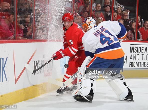 Jaroslav Halak of the New York Islanders goes behind the net to defend against Jiri Tlusty of the Carolina Hurricanes during their NHL game at PNC...