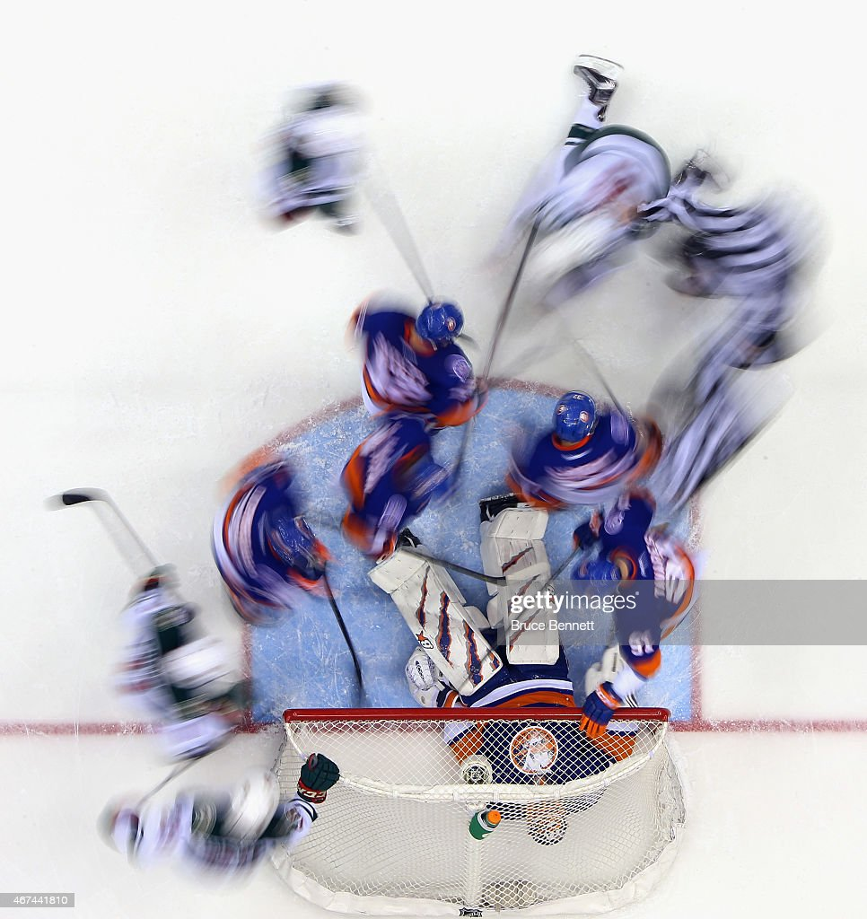 Jaroslav Halak of the New York Islanders lies on the puck as action swirls around him during the second period against the Minnesota Wild at the...