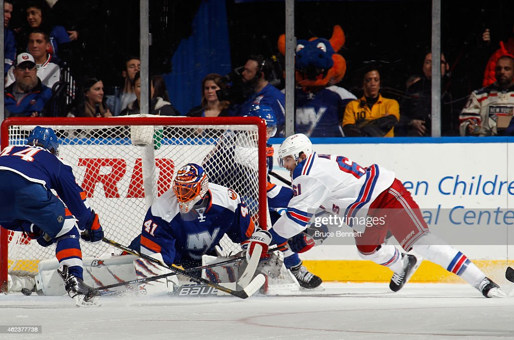 Jaroslav Halak of the New York Islanders makes the toe save on Rick Nash of the New York Rangers during the second period at the Nassau Veterans...