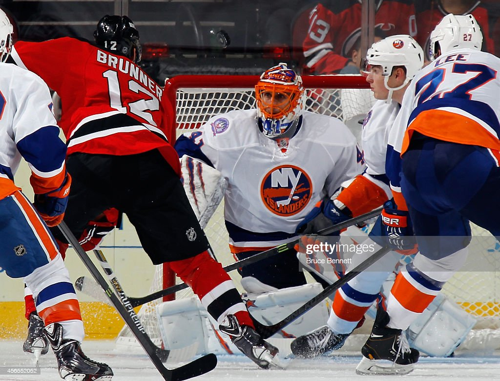 Jaroslav Halak of the New York Islanders stops Damien Brunner of the New Jersey Devils during the third period at the Prudential Center on October 2...