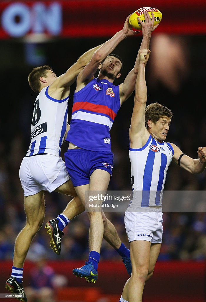 Jarrad Grant of the Bulldogs marks the ball against Shaun Atley and Nick Dal Santo of the Kangaroos (R) during the round 22 AFL match between the North Melbourne Kangaroos and the Western Bulldogs at Etihad Stadium on August 29, 2015 in Melbourne, Australia.