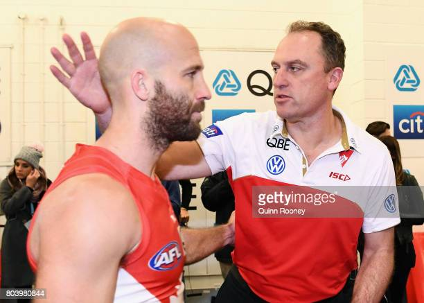 Jarrad McVeigh of the Swans is congratulated by Swans head coach John Longmire in the rooms after winning the round 15 AFL match between the...