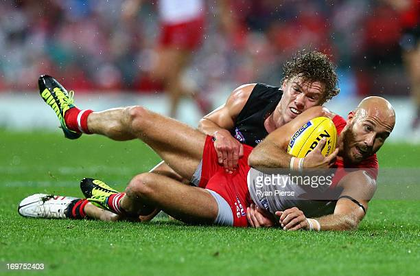 Jarrad McVeigh of the Swans is tackled by Jake Melksham of the Bombers during the round ten AFL match between the Sydney Swans and the Eseendon...