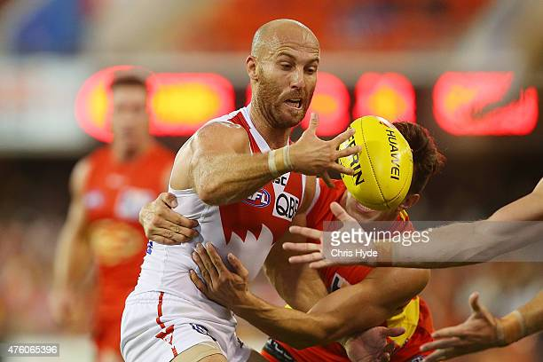 Jarrad McVeigh of the Swans is tackled during the round 10 AFL match between the Gold Coast Suns and the Sydney Swans at Metricon Stadium on June 6...