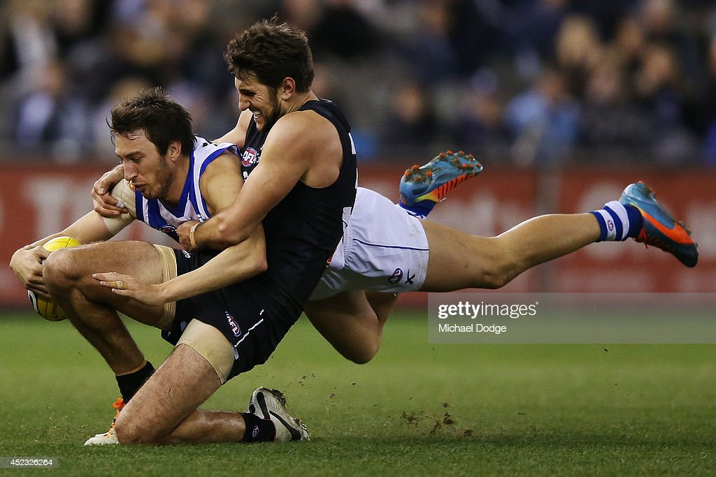 Jarrad Waite of the Blues tackles Andrew Swallow of the Kangaroos during the round 18 AFL match between the Carlton Blues and the North Melbourne Kangaroos at Etihad Stadium on July 18, 2014 in Melbourne, Australia.