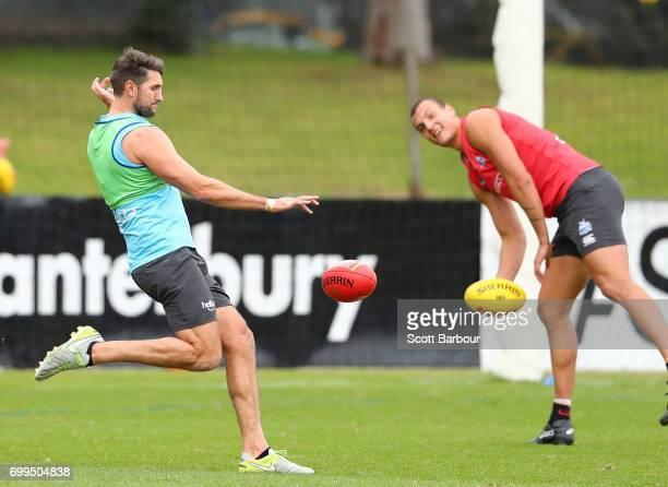 Jarrad Waite of the Kangaroos kicks the ball as Braydon Preuss of the Kangaroos look on during a North Melbourne Kangaroos AFL training session at...