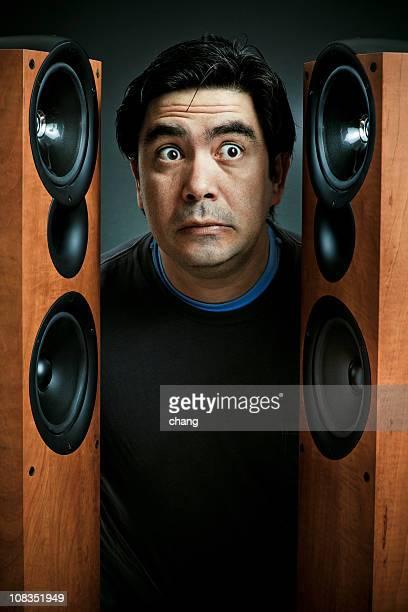 Jarred man standing in between two large brown speakers