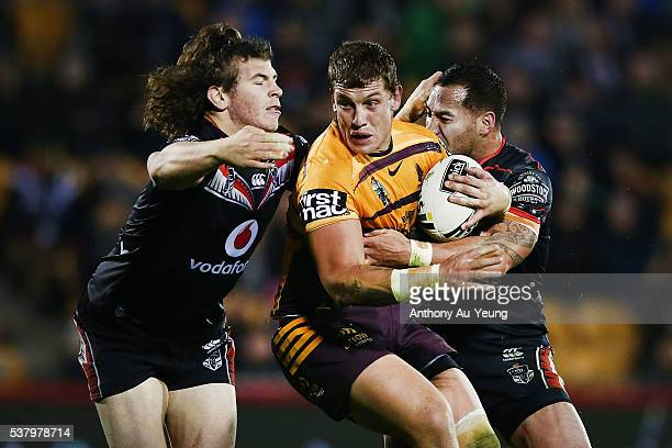 Jarred Wallace of the Broncos is tackled by Charlie Gubb and Bodene Thompson of the Warriors during the round 13 NRL match between the New Zealand...
