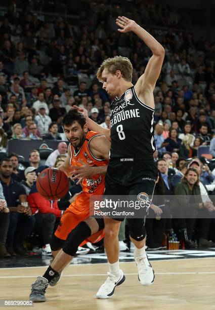 Jarred Weeks of the Cairn Taipans is challenged by Kyle Adnam of the Melbourne United during the round five NBL match between Melbourne United and...
