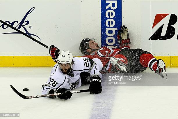 Jarret Stoll of the Los Angeles Kings and Ryan Carter of the New Jersey Devils fight for a loose puck during Game One of the 2012 NHL Stanley Cup...
