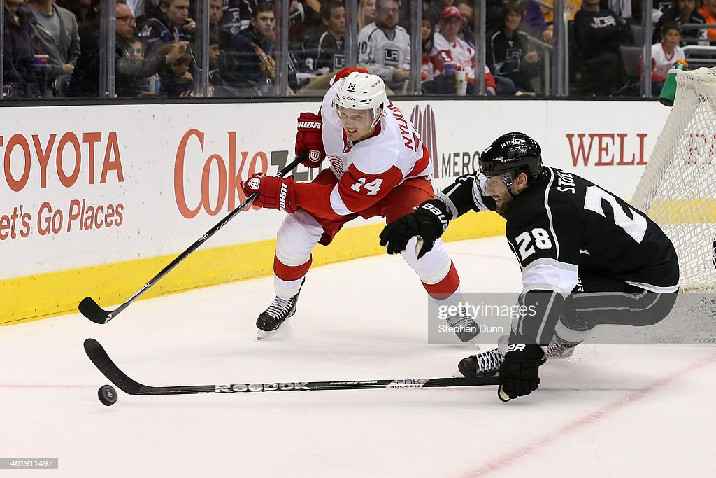 <a gi-track='captionPersonalityLinkClicked' href=/galleries/search?phrase=Jarret+Stoll&family=editorial&specificpeople=204632 ng-click='$event.stopPropagation()'>Jarret Stoll</a> #28 of the Los Angeles Kings fights for the puck with <a gi-track='captionPersonalityLinkClicked' href=/galleries/search?phrase=Gustav+Nyquist&family=editorial&specificpeople=5491209 ng-click='$event.stopPropagation()'>Gustav Nyquist</a> #14 of the Detroit Red Wings at Staples Center on January 11, 2014 in Los Angeles, California. The Red Wings won 3-1.