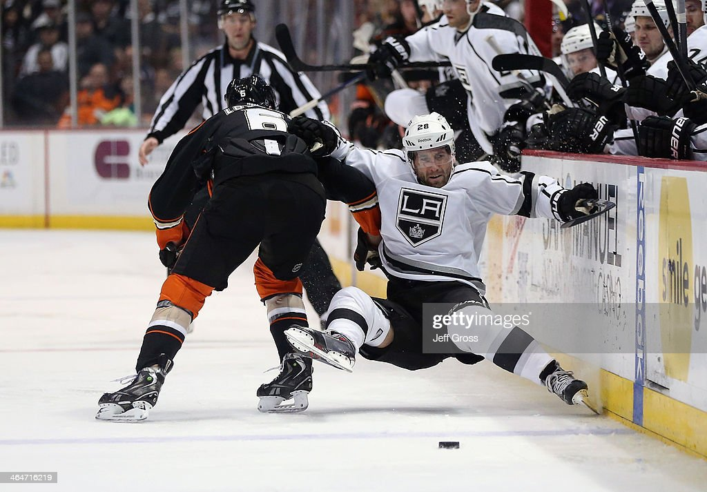 <a gi-track='captionPersonalityLinkClicked' href=/galleries/search?phrase=Jarret+Stoll&family=editorial&specificpeople=204632 ng-click='$event.stopPropagation()'>Jarret Stoll</a> #28 of the Los Angeles Kings is checked into the boards by <a gi-track='captionPersonalityLinkClicked' href=/galleries/search?phrase=Ben+Lovejoy&family=editorial&specificpeople=4509565 ng-click='$event.stopPropagation()'>Ben Lovejoy</a> #6 of the Anaheim Ducks in the second period at Honda Center on January 23, 2014 in Anaheim, California.