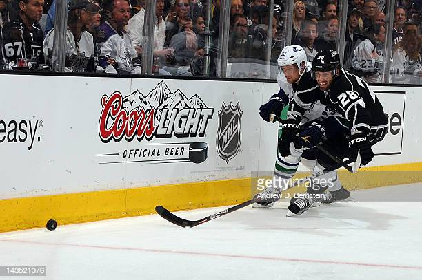 Jarret Stoll of the Los Angeles Kings reaches for the puck against Alexander Edler of the Vancouver Canucks in Game Four of the Western Conference...