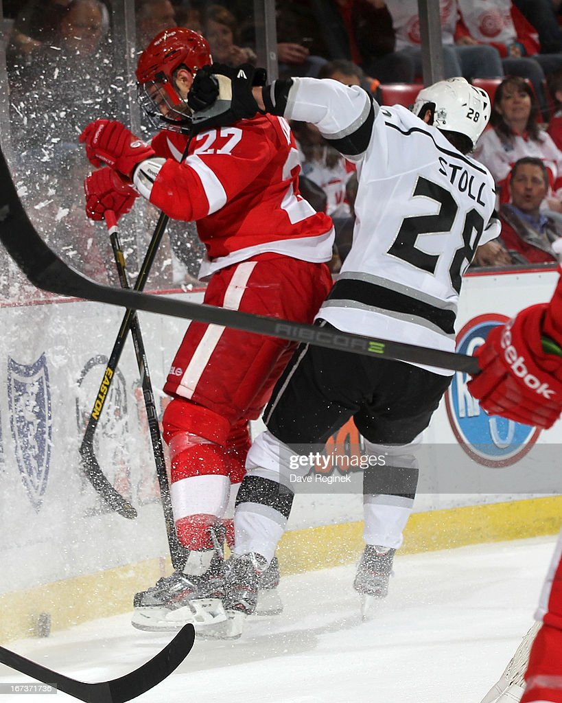 Jarret Stoll #28 of the Los Angeles Kings rides Kyle Quincy #27 of the Detroit Red Wings hard into the boards during a NHL game at Joe Louis Arena on April 24, 2013 in Detroit, Michigan.