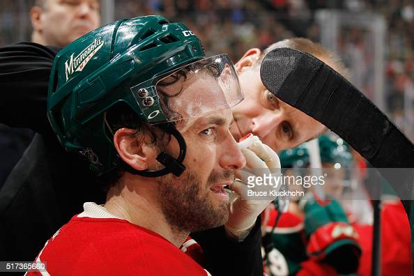 Jarret Stoll of the Minnesota Wild is treated by a trainer during the game against the Calgary Flames March 24 2016 at the Xcel Energy Center in St...