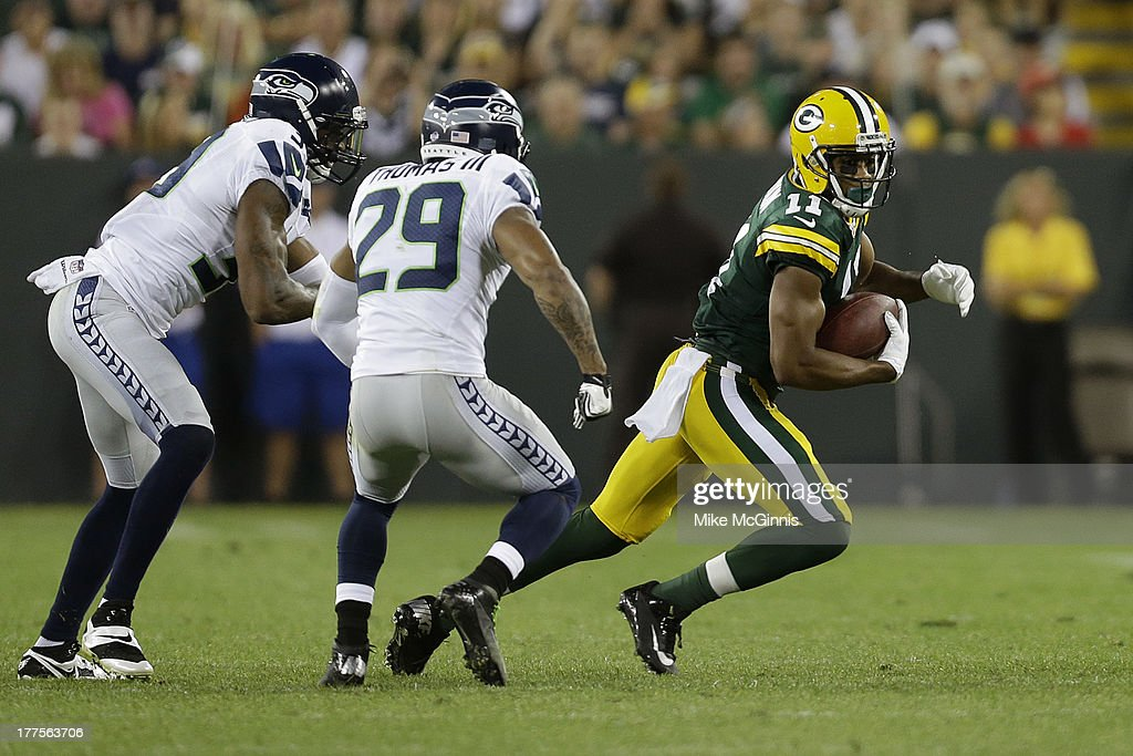 Jarrett Boykins #11 of the Green Bay Packers runs from Earl Thomas #29 of the Seattle Seahawks at Lambeau Field on August 23, 2013 in Green Bay, Wisconsin.