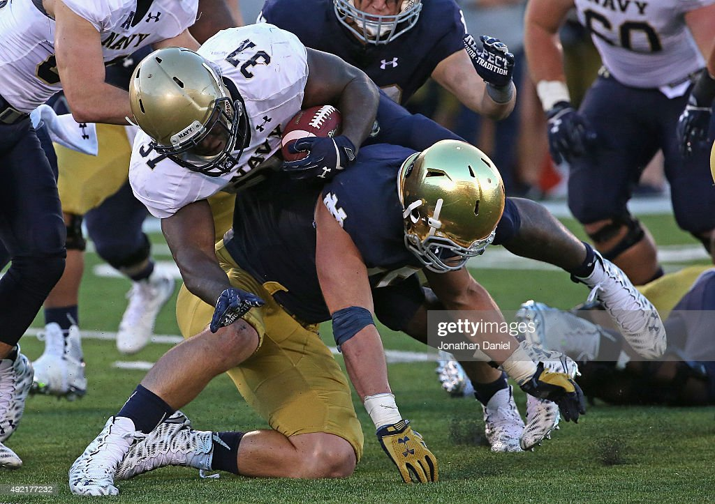 Jarrett Grace of the Notre Dame Fighting Irish upends Chris Swain of the Navy Midshipmen at Notre Dame Stadium on October 10 2015 in South Bend...