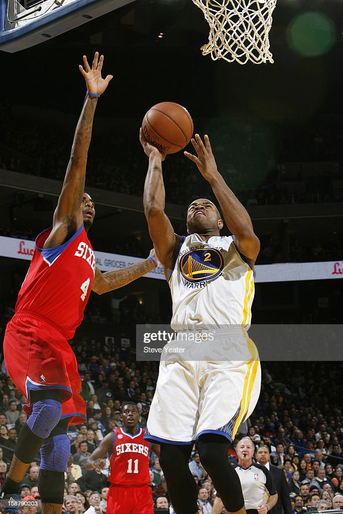 Jarrett Jack #2 of the Golden State Warriors drives to the basket against Dorell Wright #4 of the Philadelphia 76ers on December 28, 2012 at Oracle Arena in Oakland, California.