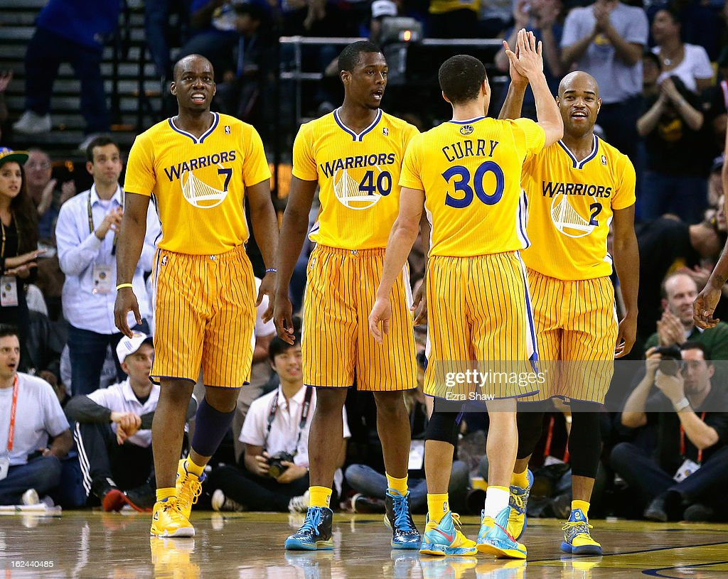Jarrett Jack #2 of the Golden State Warriors is congratulated by teammates Carl Landry #7, Harrison Barnes #40, and Stephen Curry #30 during their game against the San Antonio Spurs at Oracle Arena on February 22, 2013 in Oakland, California. The Warriors are wearing new short-sleeved uniforms for the first time. The Warriors won the game in overtime.
