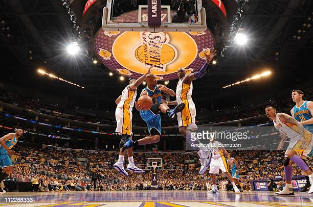 Jarrett Jack of the New Orleans Hornets looks to pass between Andrew Bynum and Lamar Odom of the Los Angeles Lakers in Game One of the Western...