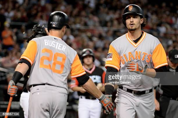 Jarrett Parker of the San Francisco Giants is congratulated by Buster Posey wearing a nicknamebearing jersey after hitting a solo home run in the...