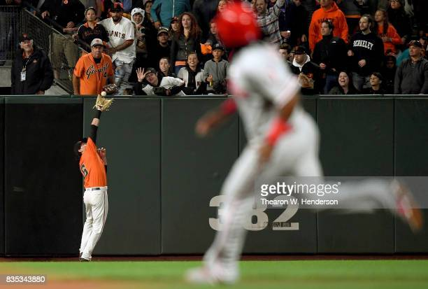 Jarrett Parker of the San Francisco Giants runs back to the wall to catch a fly ball taking a hit away from Tommy Joseph of the Philadelphia Phillies...