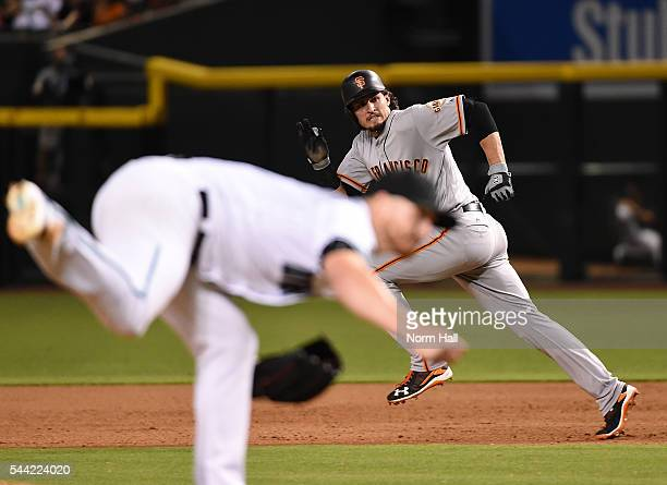 Jarrett Parker of the San Francisco Giants runs from first to second base while looking back at home plate as Shelby Miller of the Arizona...