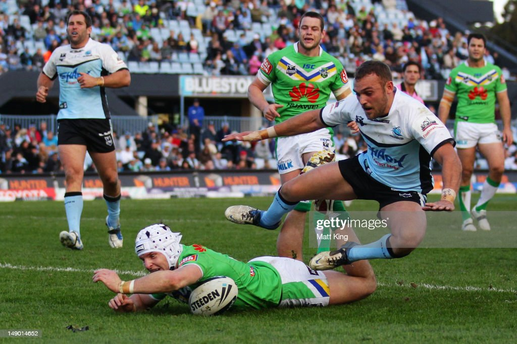 Jarrod Crocker of the Raiders scores a try as Isaac Gordon of the Sharks jumps over the top during the round 20 NRL match between the Cronulla Sharks...