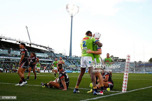 Jarrod Croker of the Raiders celebrates with team mate Edrick Lee after scoring a try during the round 20 NRL match between the Canberra Raiders and...
