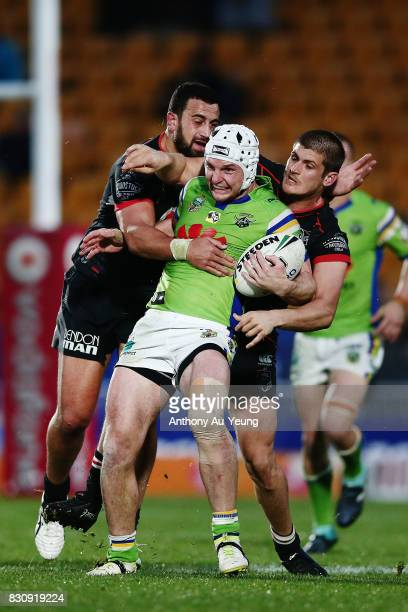 Jarrod Croker of the Raiders is tackled by Ben Matulino and Blake Ayshford of the Warriors during the round 23 NRL match between the New Zealand...