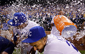 Jarrod Dyson and Christian Colon of the Kansas City Royals are doused with water by catcher Salvador Perez after the Royals defeated the Cleveland...