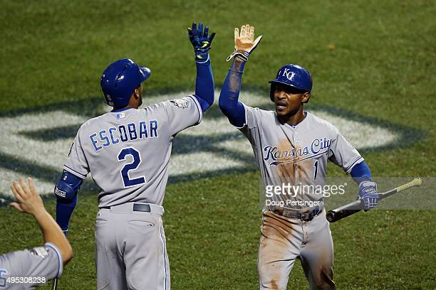 Jarrod Dyson of the Kansas City Royals celebrates with Alcides Escobar after scoring the go ahead run hit by Christian Colon in the twelfth inning...