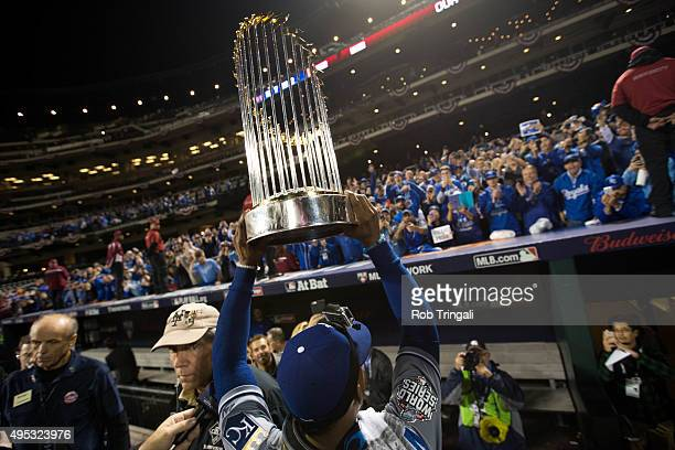 Jarrod Dyson of the Kansas City Royals is seen on the field with the Commissioner's Trophy after defeating the New York Mets in Game 5 of the 2015...