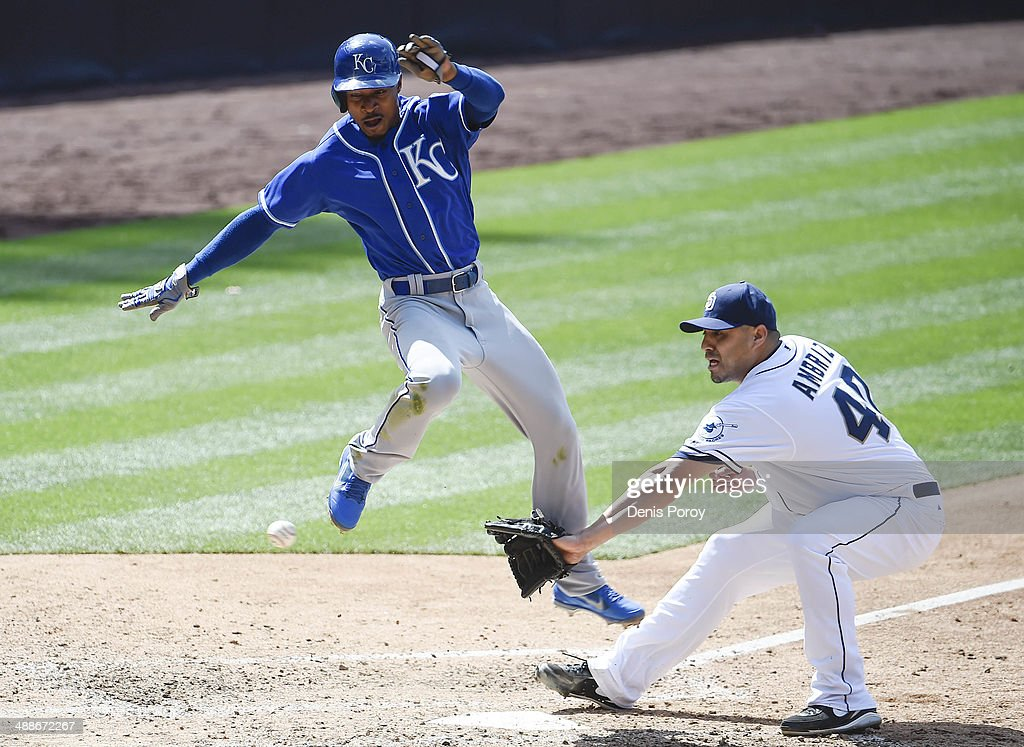 Jarrod Dyson #1 of the Kansas City Royals jumps as he scores past the throw to Hector Ambriz #40 of the San Diego Padres during the eighth inning of a baseball game at Petco Park May 7, 2014 in San Diego, California.