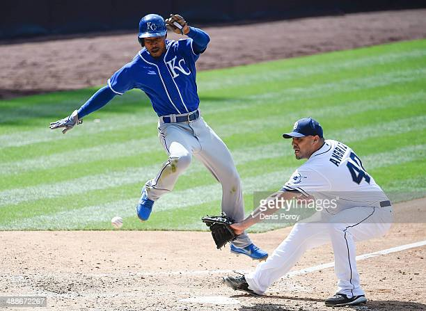Jarrod Dyson of the Kansas City Royals jumps as he scores past the throw to Hector Ambriz of the San Diego Padres during the eighth inning of a...