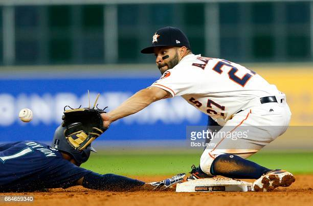 Jarrod Dyson of the Seattle Mariners gets his hand on the bag before Jose Altuve of the Houston Astros can apply the tag in the ninth inning at...