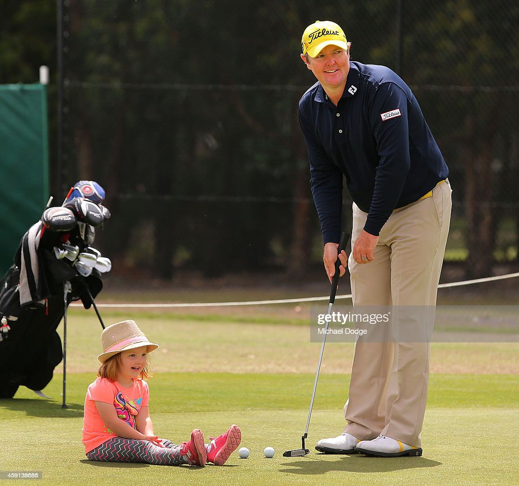 <a gi-track='captionPersonalityLinkClicked' href=/galleries/search?phrase=Jarrod+Lyle&family=editorial&specificpeople=210982 ng-click='$event.stopPropagation()'>Jarrod Lyle</a> of Australia putts on the practice green with daughter Lucy Lyle watching ahead of the 2014 Australian Masters at The Metropolitan Golf Course on November 18, 2014 in Melbourne, Australia.