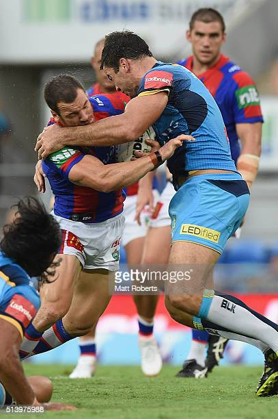 Jarrod Mullen of the Knights is tackled by David Shillington of the Titans during the round one NRL match between the Gold Coast Titans and the...